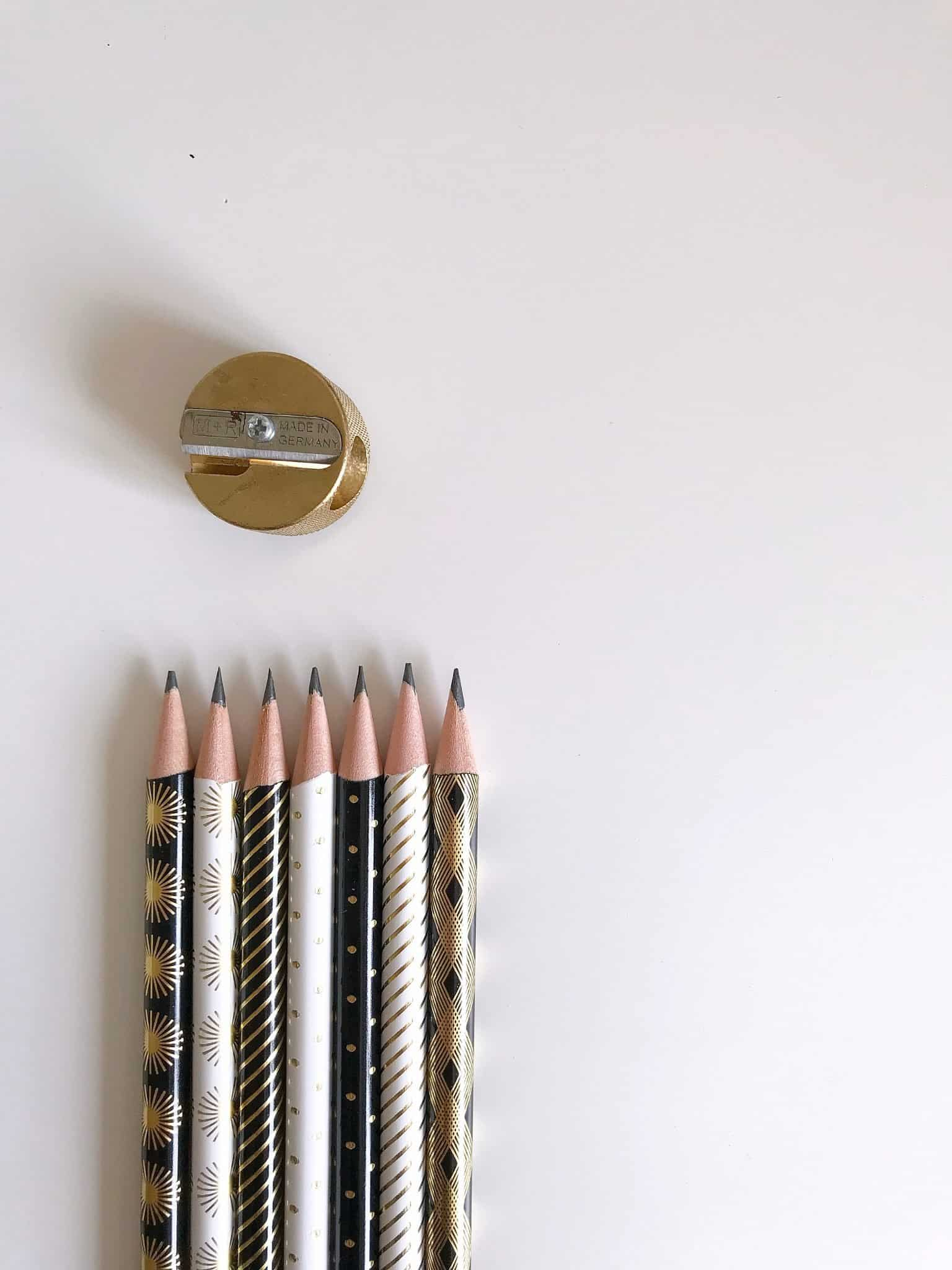 Black, white and gold pencils with a gold pencil sharpener