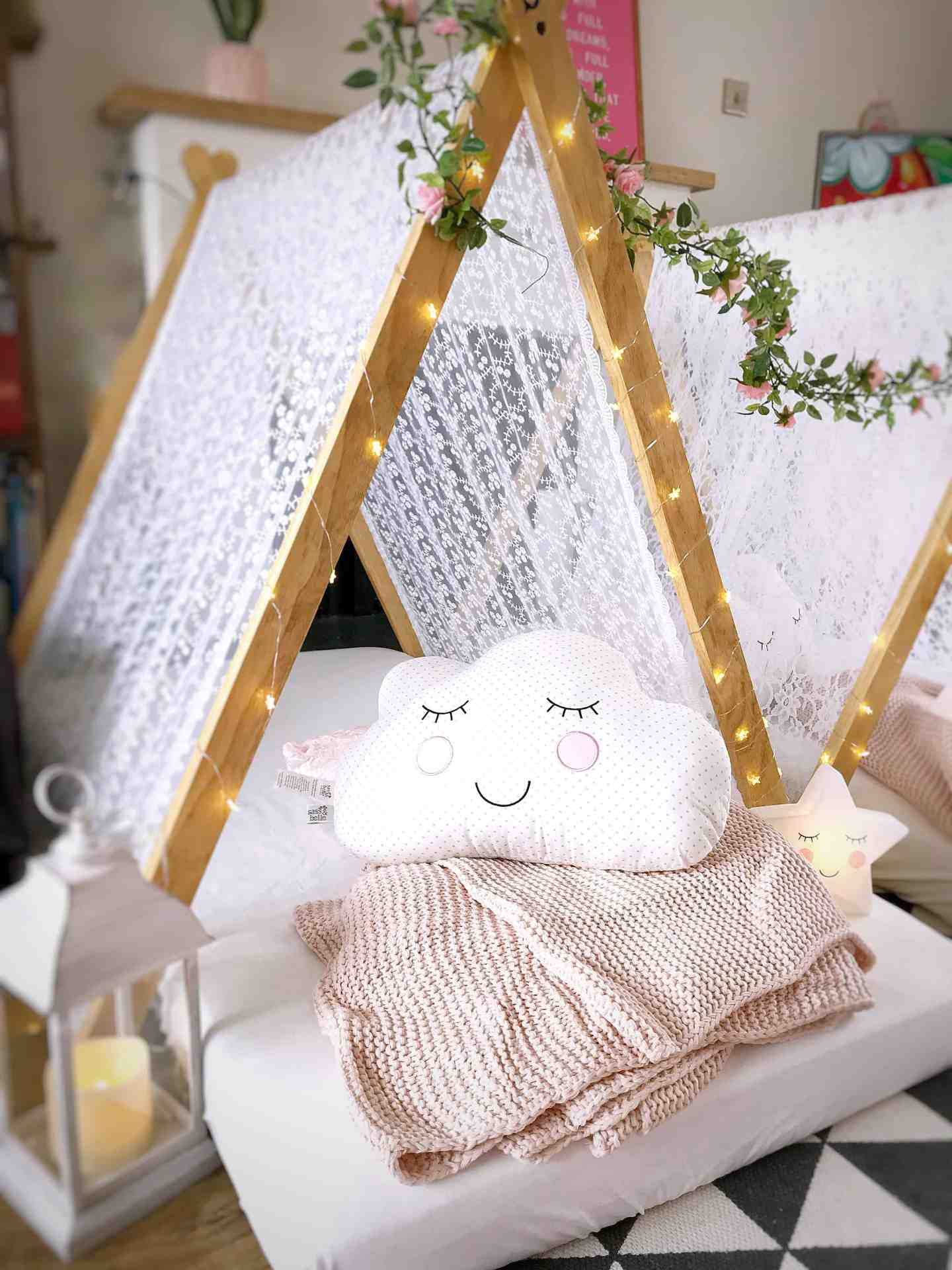 A cosy tent with lantern, pink blanket, cloud cushion and fair lights at our kids tee pee party