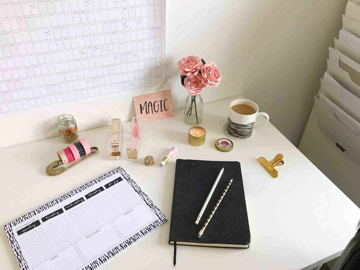 White desk space with academic wall planner, desk planner, noteboo and gold desk accessories