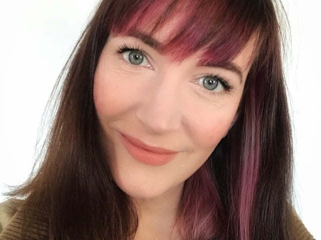 Becky Pink wearing products from the Green People natural beauty advent calendar, including Age Defy 24 Hours Brightening, Day Solution Cream SPF15, Velvet Matte Lipstick in Damask Rose, Illuminating Eye Shadow and Black Volumising Mascara