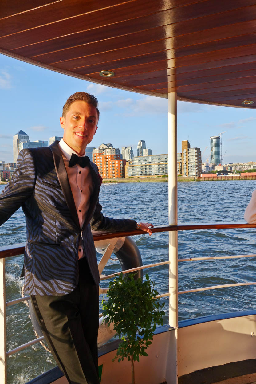 Antoine posing with Canary Wharf and Pan Peninsula in the background aboard the MV Edwardian on the Thames, London