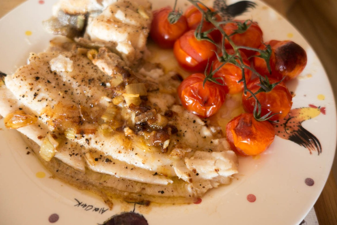 Dinner of pan-fried Cornish lemon sole with roasted vine cherry tomatoes