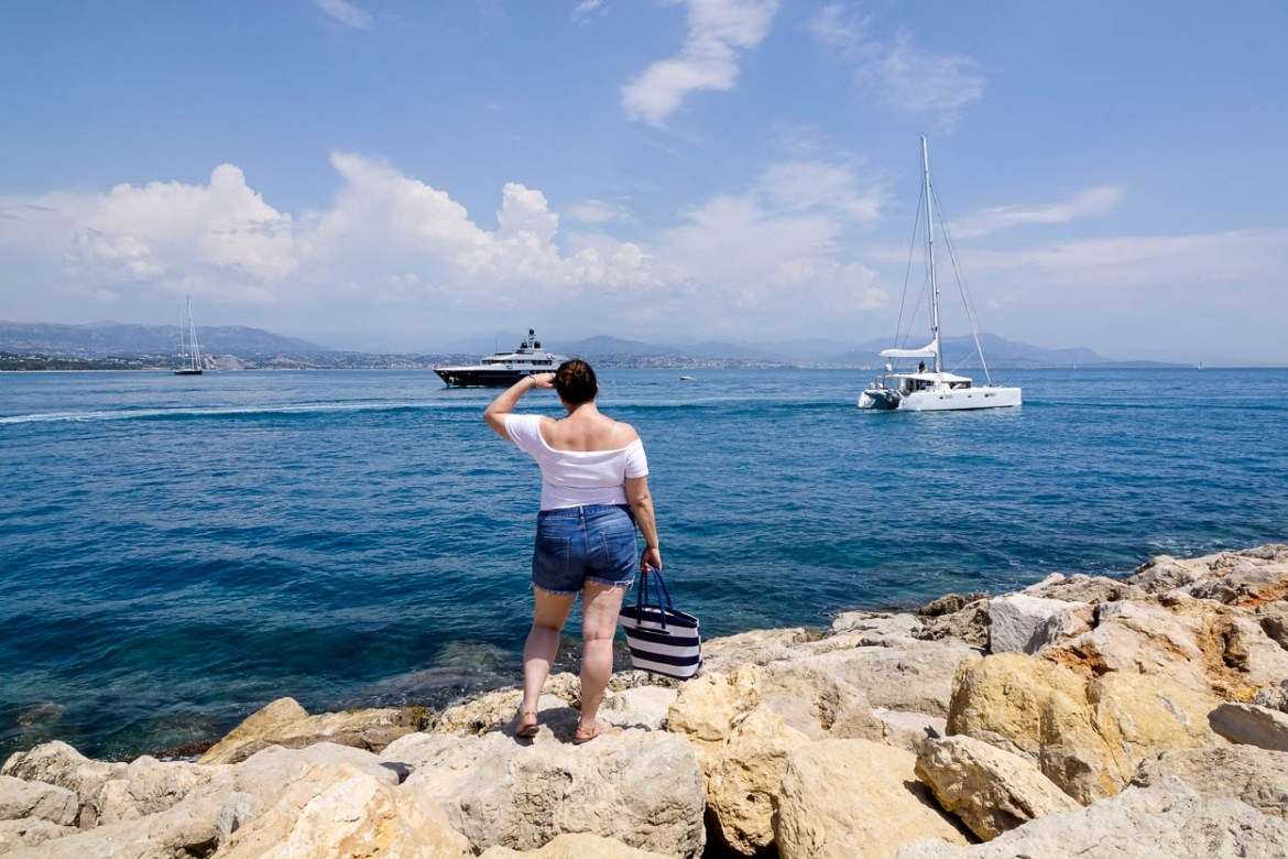 pinkschmink looks out over the Baie Des Anges as two yachts pass at Port Vauban, Antibes