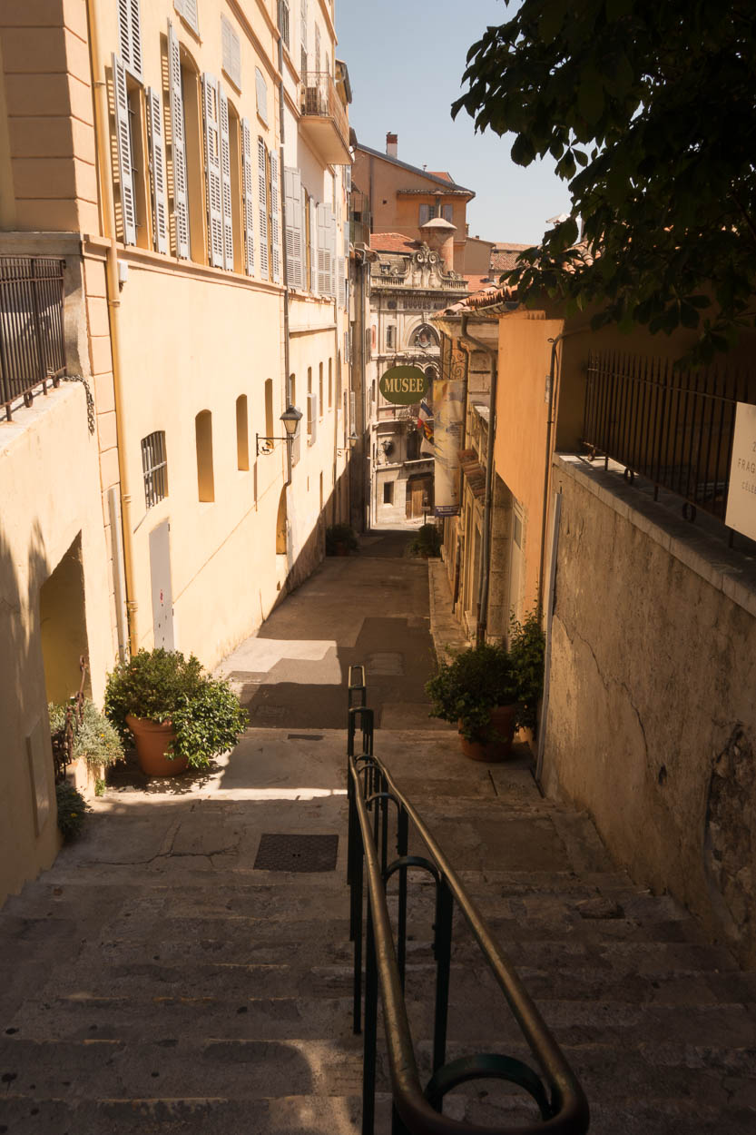 Steps down to paved streets between yellow-painted buildings in Grasse