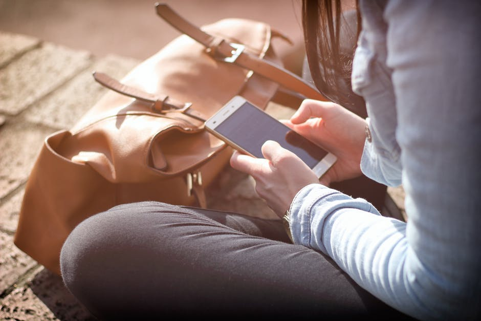 woman looking at mobile phone apps