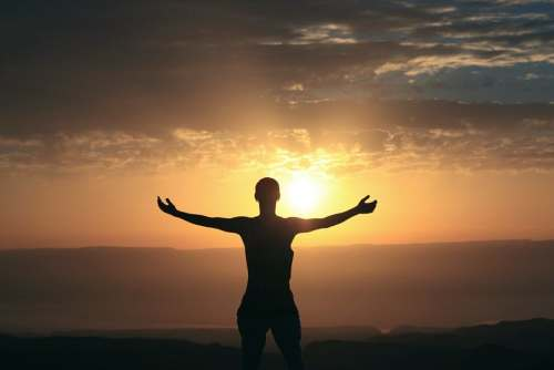 man standing with arms open backlit by sunrise