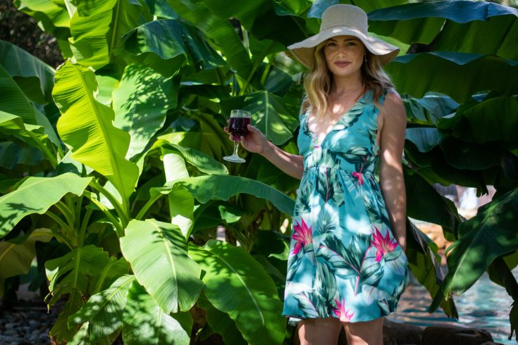 Elizabeth, a white female, is seen wearing an Amy Nicole Studio Chelsea Party Dress that she sewed from a Teal Tropics crepe rayon in a bold pink floral print on a teal background with palm leaves. She is wearing a straw beach hat, standing in front of large, leafy banana plants, and holding a glass of sangria.