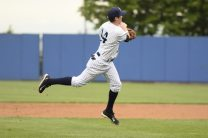 Kyle Holder in the air as he attempts to get the runner at first (Robert M Pimpsner)