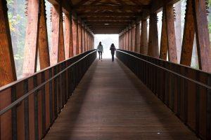 Photo of two people walking across the bridge.