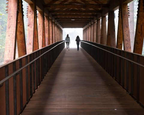 Photo of two people walking across the bridge.