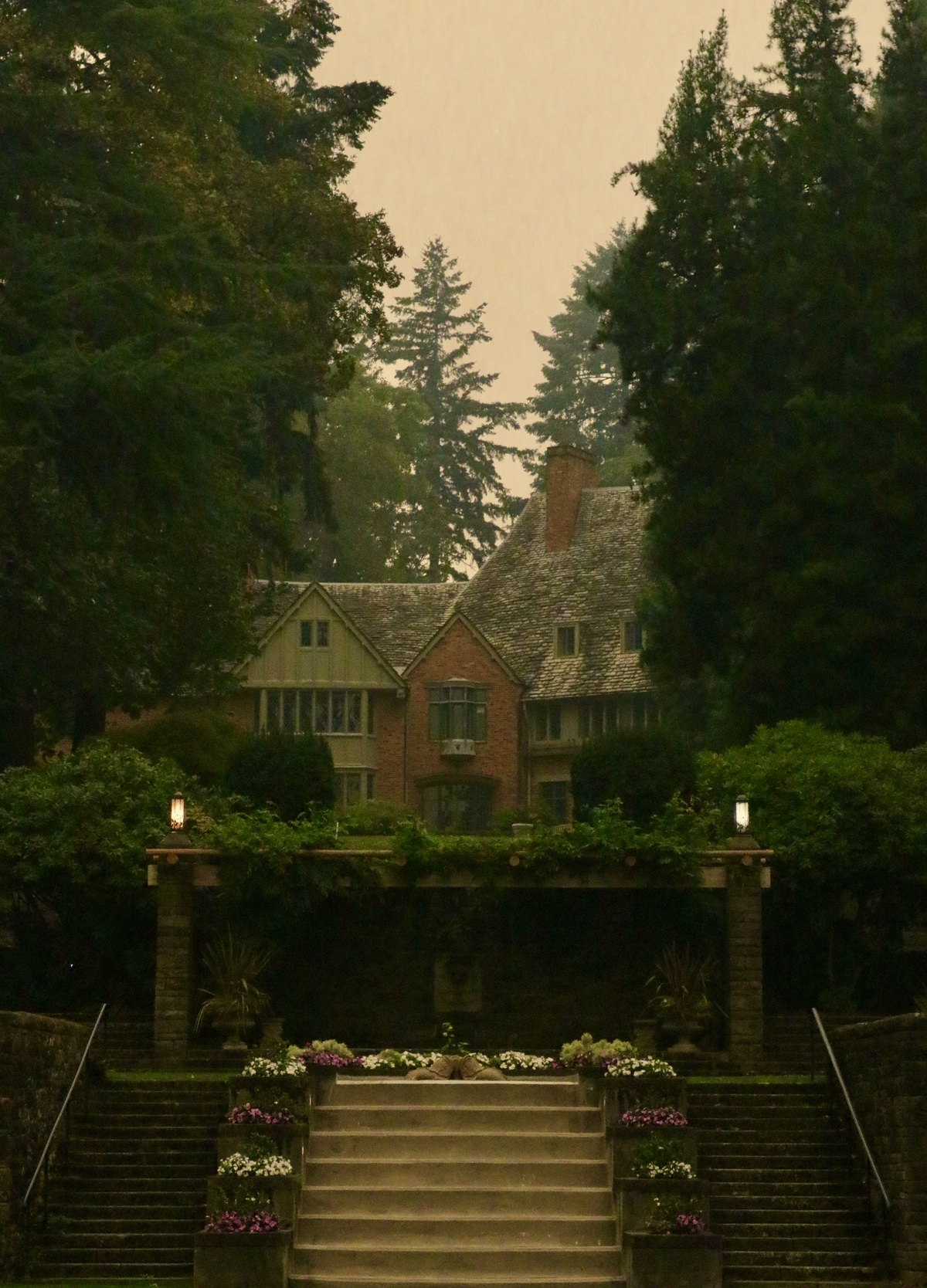 Photograph of Frank Manor House from the perspective of the Reflecting Pool in the foreground and a smoke-filled sky in the background.