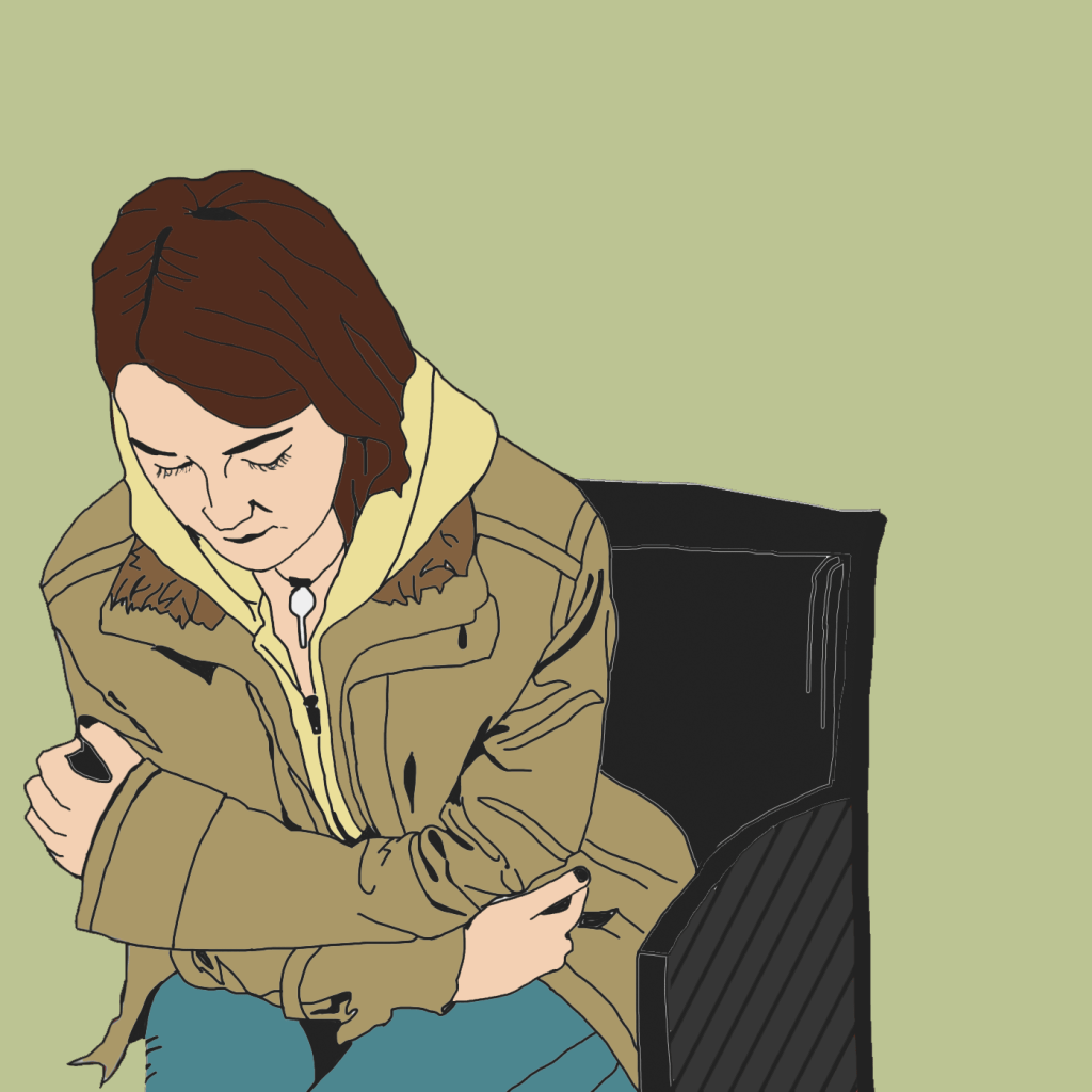 A teenage girl sits sadly in a chair