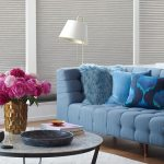 Blue couch with pink flowers in vase