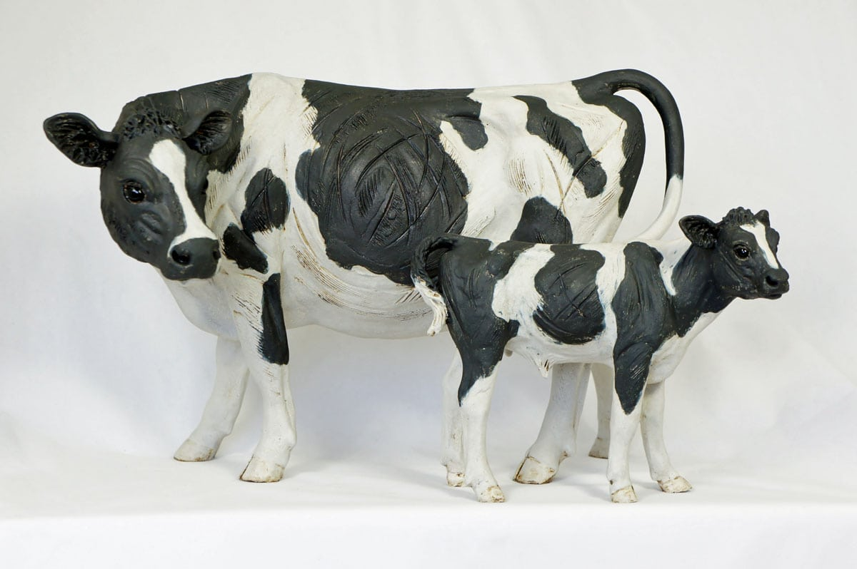 A Black and White Cow with Calf - ceramic clay sculpture