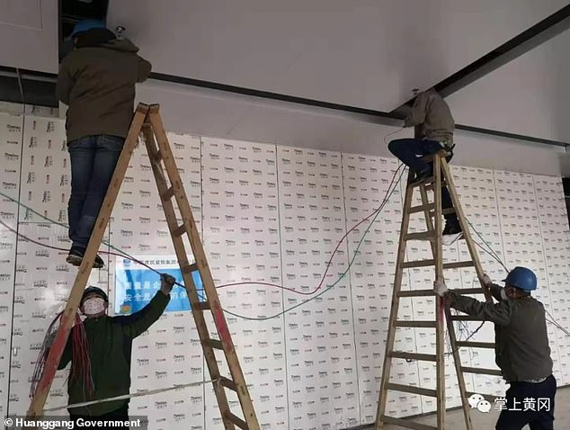 A handout from the Huanggang government shows workers from the city's electricity company working to connect the building to the grid so it can treat coronavirus patients