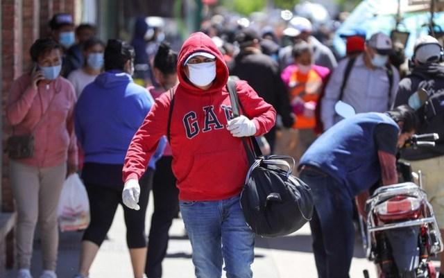 Uma foto que mostra pessoas de máscara contra Covid andando na rua