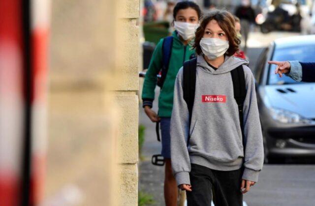 Uma foto dos estudantes indo à escola de máscara
