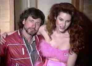 "pirromount actress Monique Parent sits on the lap of director Mark Pirro on the set of ""Buford's Beach Bunnies"" (1992)"