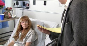 Raven (Stef Dawson), in a hospital bed, is questioned by attorney Chet Neimano (Doug MacPherson).