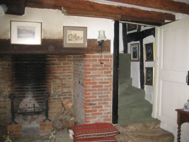 Inserted chimney with large open ground floor fireplace. The staircase to the side twists tightly around the flue providing access to the newly created room above this former open hall. The low height of the tie beam prevented access from this staircase initially to the first floor room beyond which would have always been accessible directly by an open ladder type stair. Later alterations after the new wing to the side was built, included cutting through the tie beam to allow access to both rooms from this staircase.