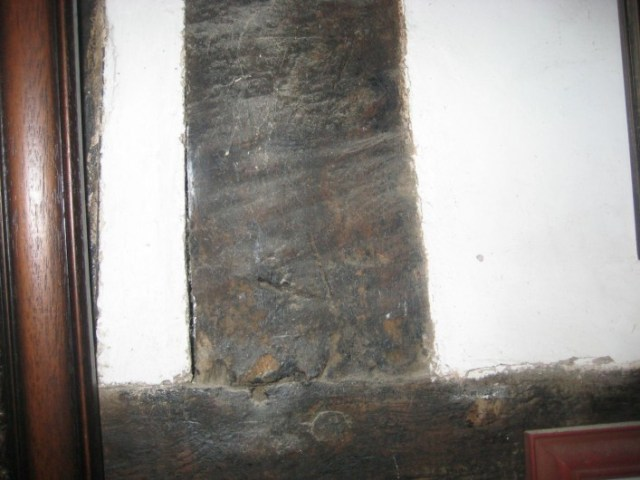 The original south western outside wall became an internal wall when the new wing was added preserving a series of carpenters marks marking the position of studs in the framework. This one is marked V.