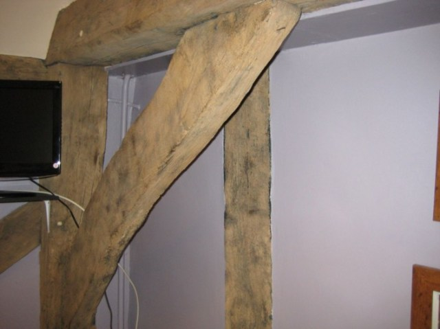 Former end wall shown by the tie beam and brace with the wall of the crosswing visible beyond. Although part of the tie beam is restricted from view, there is no sign of studs connecting into the tie beam. This may have been open to another bay which was demolished when the cross wing was built.