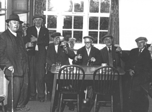 1973  Pensioners enjoying their lunchtime pint in the front bar. L-R: Bob Males, Arthur Cooper, Frank Knight, Donald Hoy, Ernie Lake, Alf Agar. The other public bar was the large clubroom at the back which was used by village organisations before the Village Hall was built. May's son Derek Cook recounts the tale of smoking contests which took place here. The winner was the smoker who could make a pipe full of tobacco last the longest.