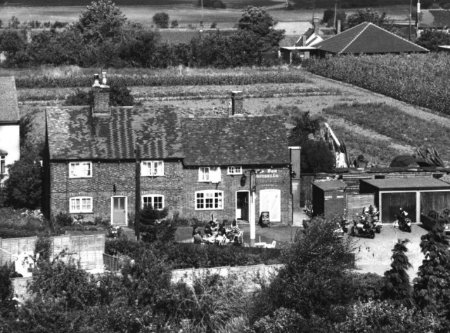 The Fox public house with Colemans Close behind. All the pubs in the village except the Motte and Bailey began around 1830 as beerhouses. The abolition of licensing requirements for beerhouses at that point meant that anyone who paid the 2 Guineas excise payment could sell beer. Most beer retailers combined this activity with another job. John Walker, who took over the Fox in 1912, was also a higgler, a collector and seller of eggs. Pigs and horses were kept in the close to supplement his income.