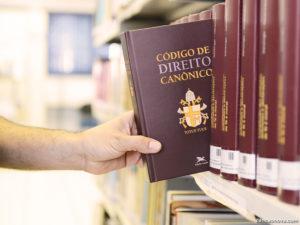 Mão pega Codigo de Direito Canonico na Estante