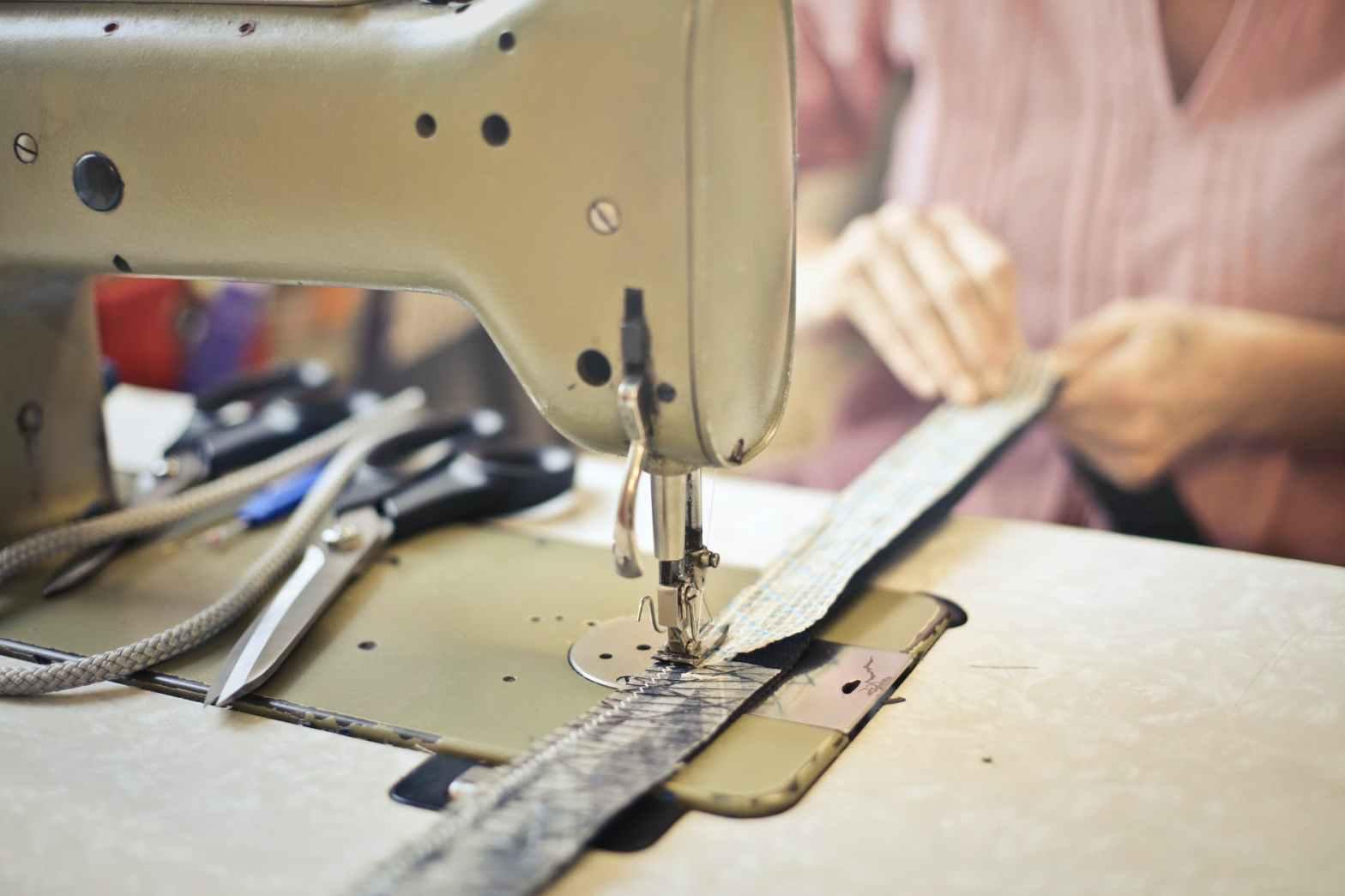 seamstress stitching clothing item on sewing machine