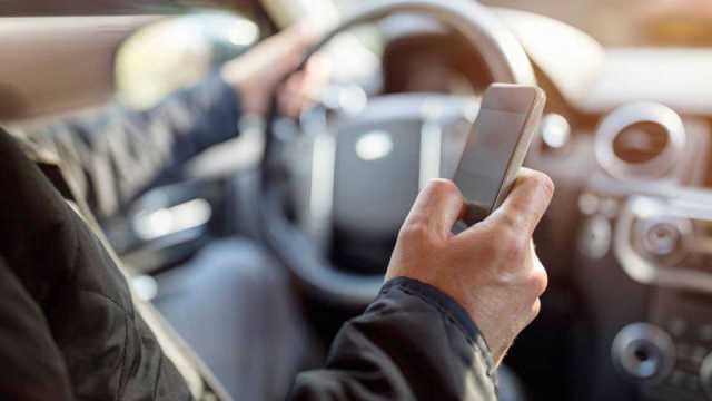 Conductor utilizando el móvil mientras está en marcha infringiendo las normas de tráfico