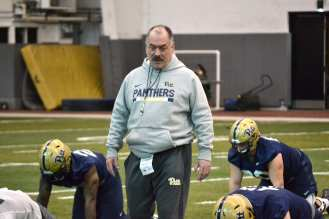New offensive line coach Dave Borbely supervises some stretching.