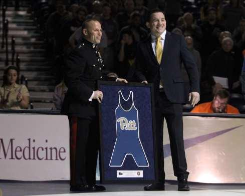 Head Coach Keith Gavin presents Major General Daniel J. Lecce a framed singlet December 15, 2018 -- David Hague/PSN