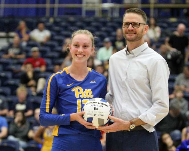 Stephanie Williams (13) receives the game ball for her 1000th career kill from Volleyball head coach Dan Fisher October 5, 2018 -- DAVID HAGUE