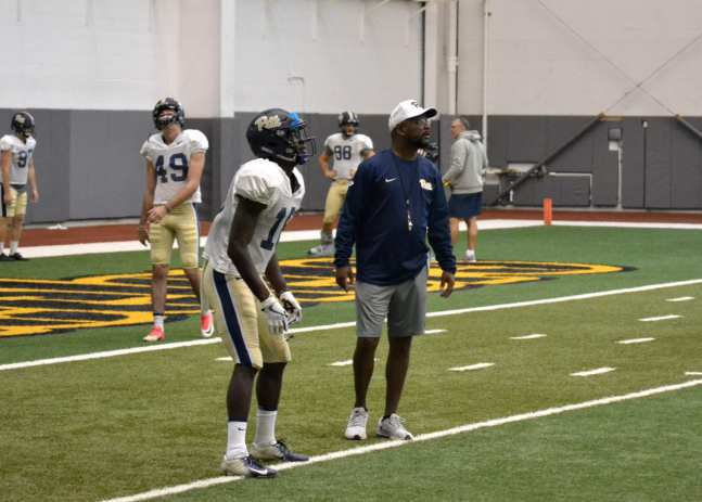Pitt WR Shocky Jacques-Louis fields a punt while receivers coach Kevin Sherman looks on at practice Sept. 18, 2018