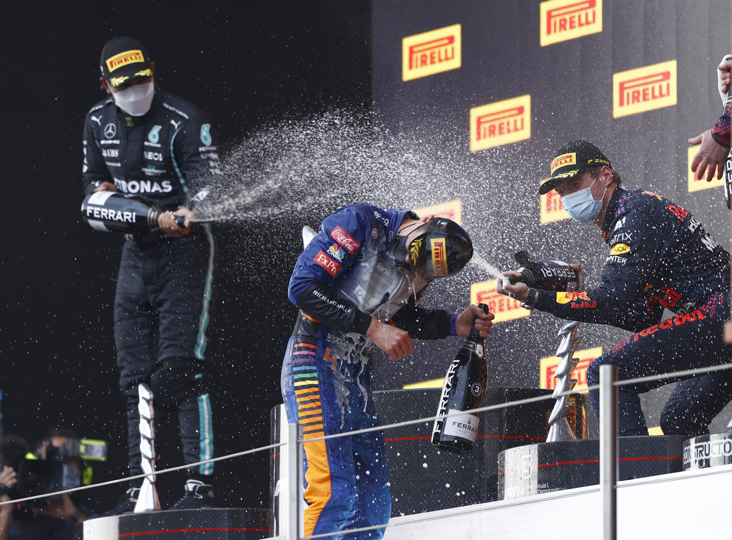 Sir Lewis Hamilton, Mercedes, 2nd position, Max Verstappen, Red Bull Racing, 1st position, Lando Norris, McLaren, 3rd position, and the Red Bull trophy delegate spray Champagne