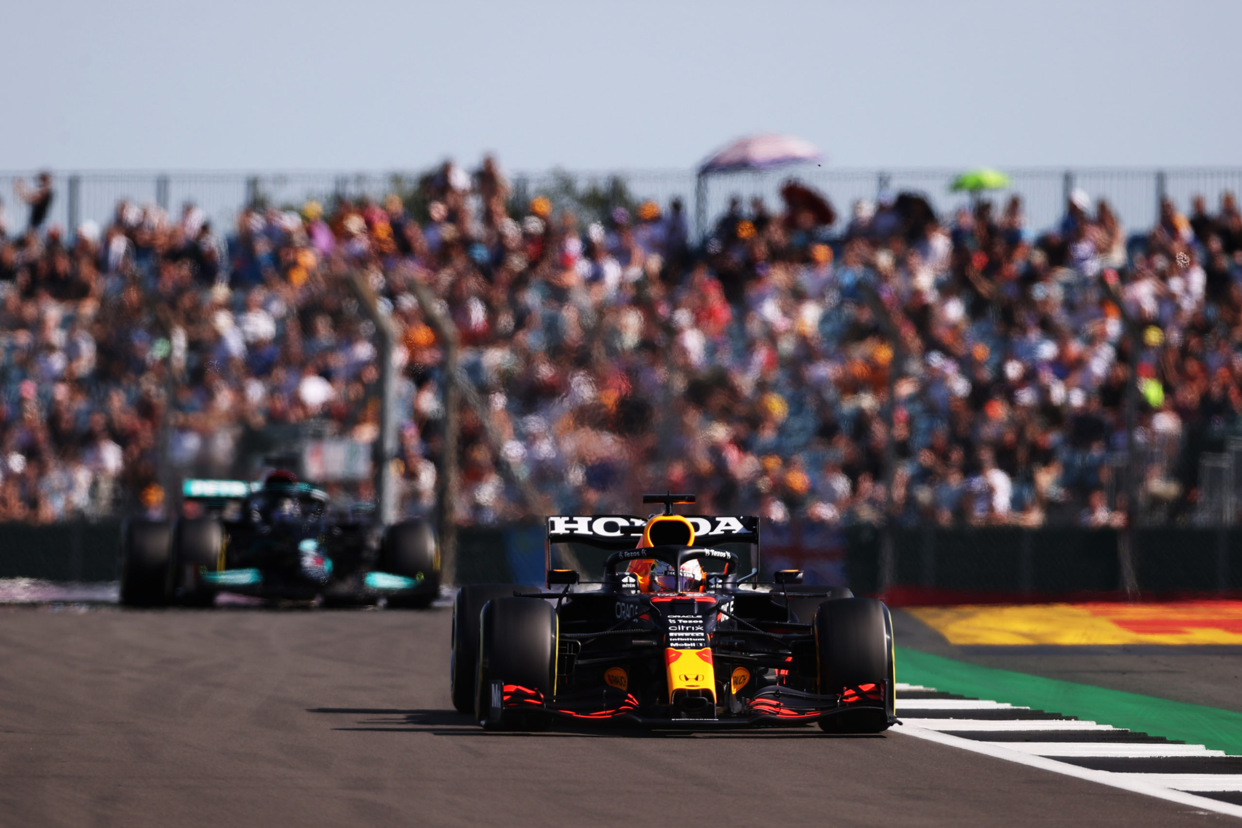 NORTHAMPTON, ENGLAND - JULY 17: Max Verstappen of the Netherlands driving the (33) Red Bull Racing RB16B Honda leads Lewis Hamilton of Great Britain driving the (44) Mercedes AMG Petronas F1 Team Mercedes W12 during the Sprint for the F1 Grand Prix of Great Britain at Silverstone on July 17, 2021 in Northampton, England. (Photo by Lars Baron/Getty Images) // Getty Images / Red Bull Content Pool  // SI202107170352 // Usage for editorial use only //