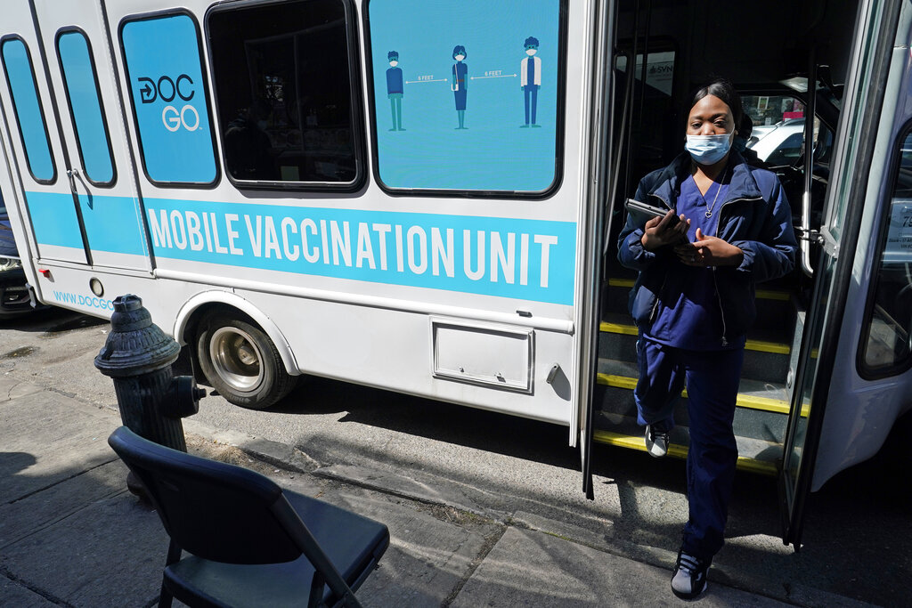 A health care worker steps out of a mobile vaccination van in Brooklyn