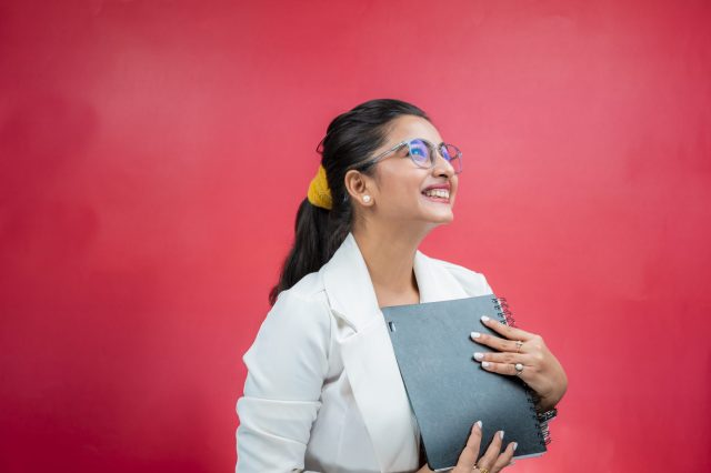 Happy Girl With Notebook on Red Background
