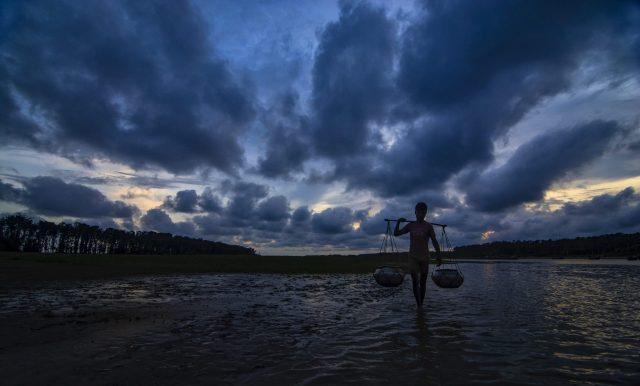 A fisher walking on Talsari Beach