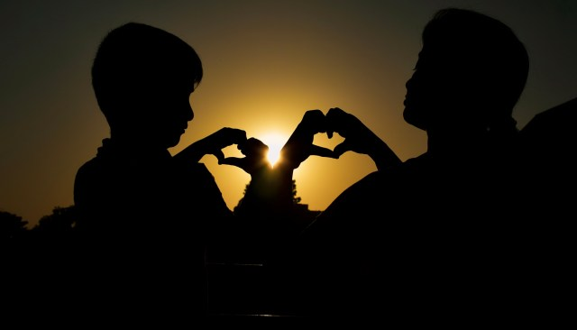 A girl and a boy making love hand signs.