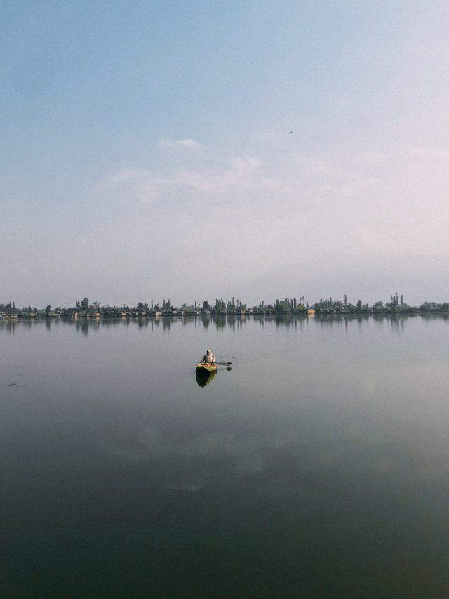 Man canoeing on large lake alone