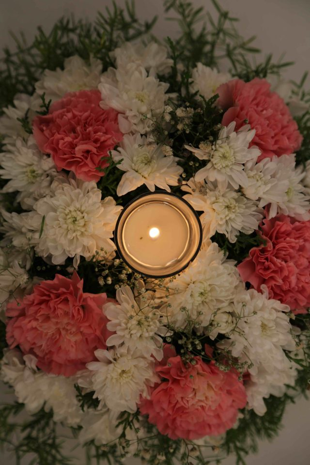Candle between bouquet of flower