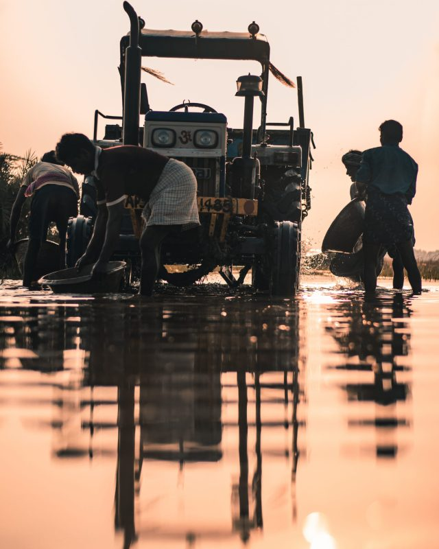People washing a tractor in a pond