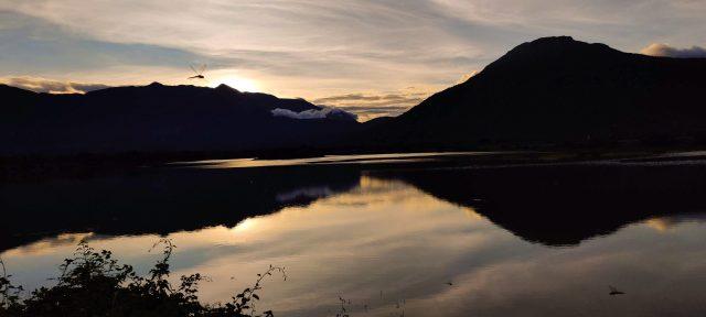 Sunset through mountains and lake
