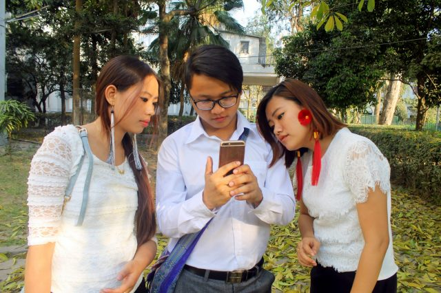 Three college friends checking mobile