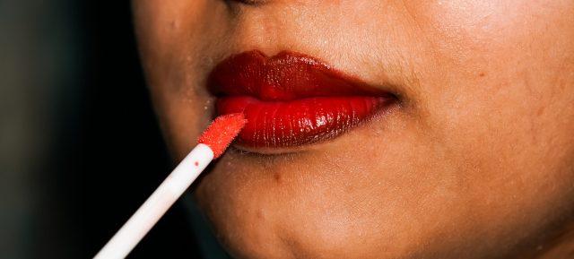 A girl applying, color on lips