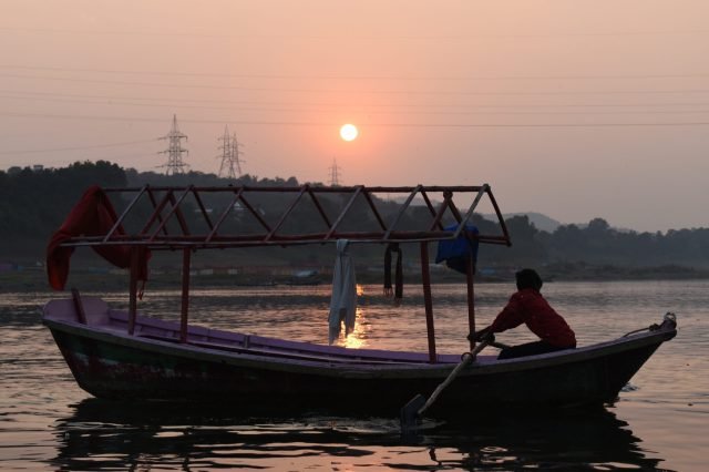 man paddeling boat in water during sunset