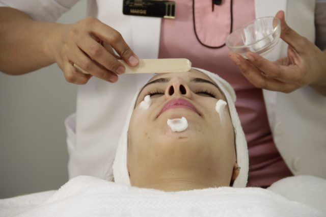 Beautician applying face mask on women
