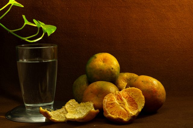 Fresh oranges and glass of water